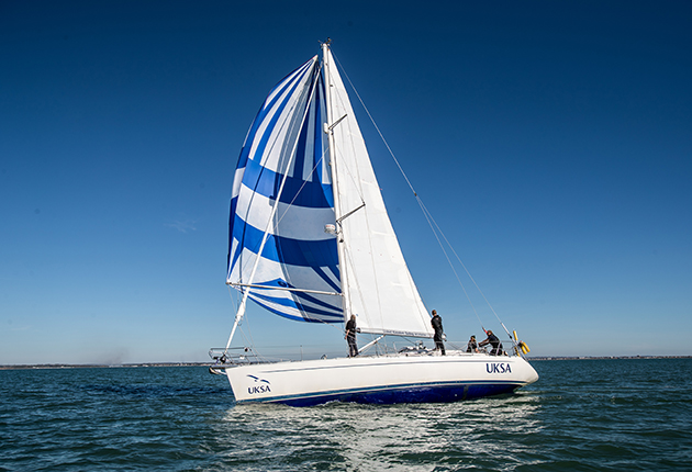 A yacht with a blue and white sail