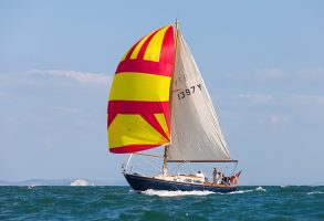 A yacht flying a yellow and red spinnaker sail