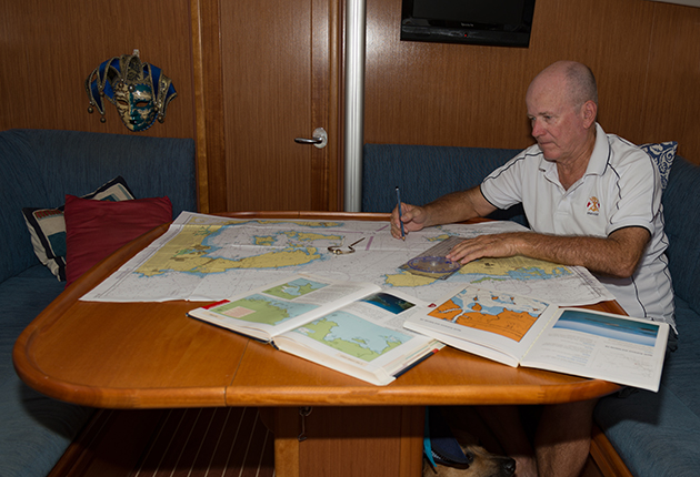 A man sitting at a table looking at charts on a yacht
