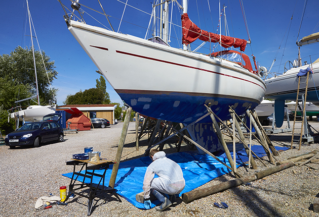 A man in PPE preparing to antifoul his yacht