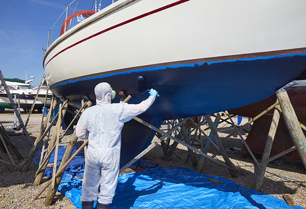 A man wearing protective gear to antifoul a boat