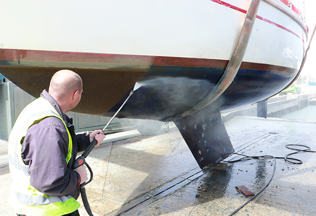A man pressure washing the hull of a boat ahead of antifouling