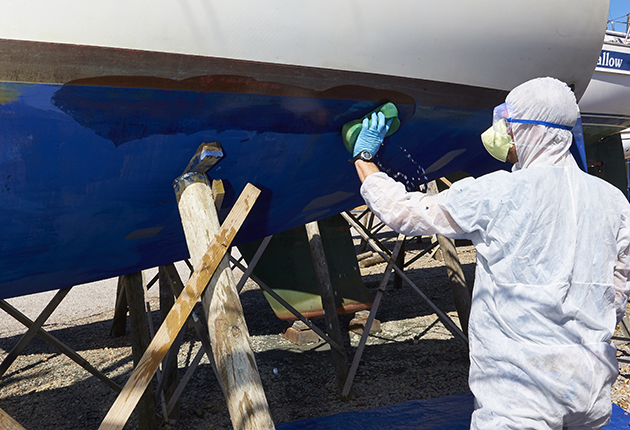 A MAN In PPE sandpapering the hull of a yacht