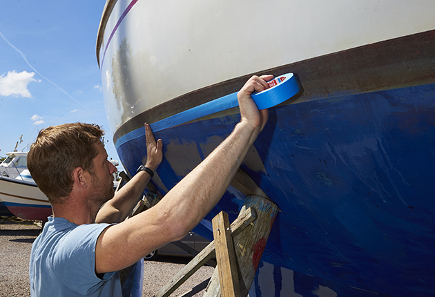 A man masking off the side of a yacht ahead of applying antifoul