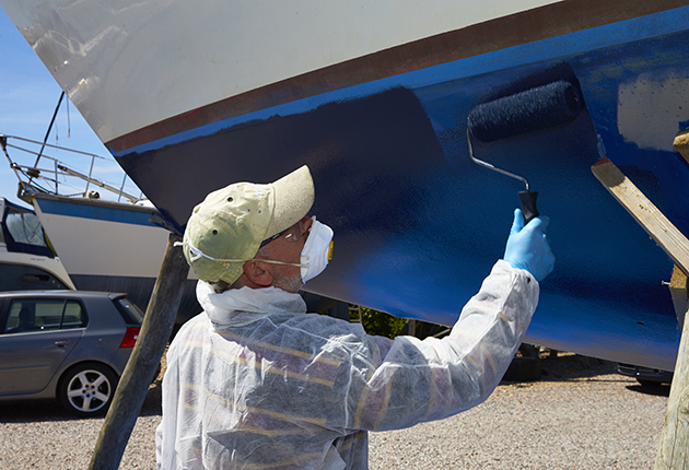 A man in PPE applying antifoul to the hull of a yacht