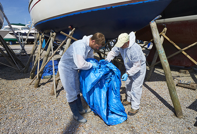 Two men carrying tarp out from underneath a yacht