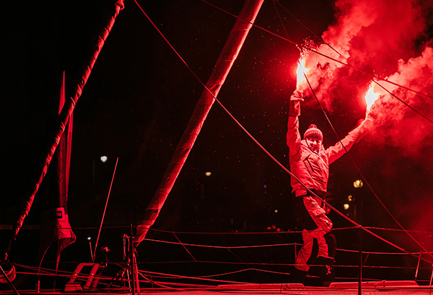 Pip Hare holding lit flares as she celebrates crossing the finish line of the 2021-21 Vendee Globe