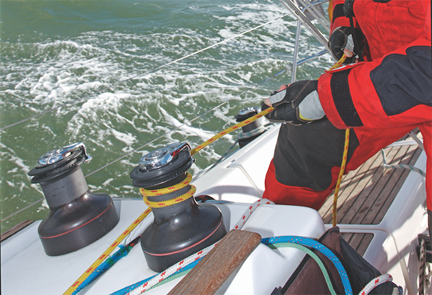 A sailor pulling on a rope around a winch on a boat