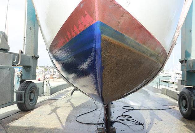 A yacht with antifoul, with one side of the hull washed down after a season in the water