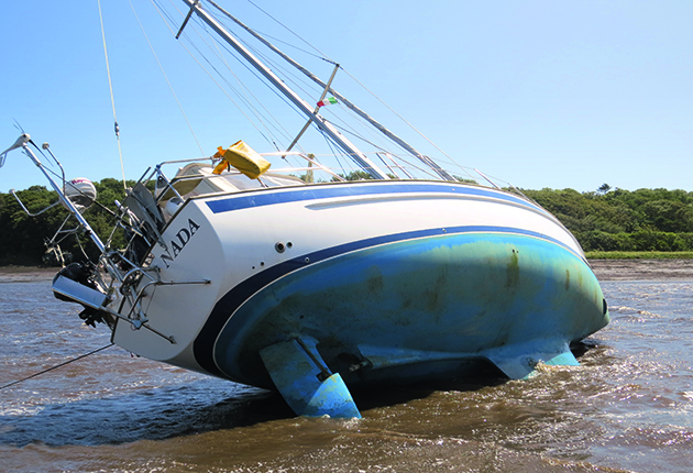 A yacht that has run aground on a river