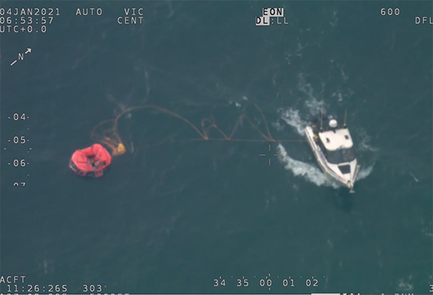 A man is rescued from the water by a police boat off the coast of Australia