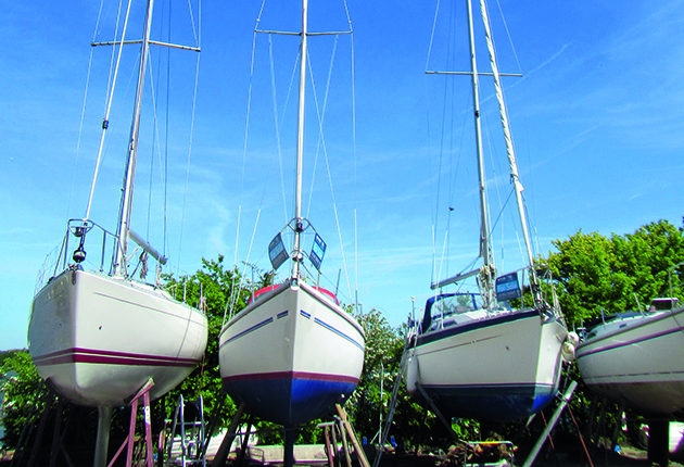 Three boats for sale lined up in a brokerage yard