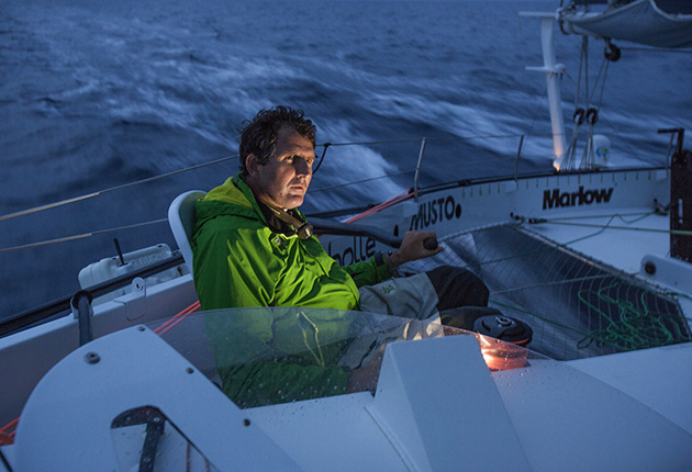 A man on a cockpit of a boat, wearing a green jacket