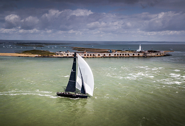 A yacht with black and white sails sailing out of a harbour under a dark sky