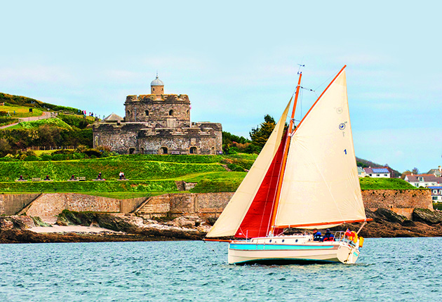 Small yacht with red and white sails passing St Mawes Castle on the Roseland peninsula in Cornwall UK