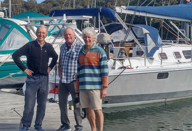 Three men standing in front of a yacht