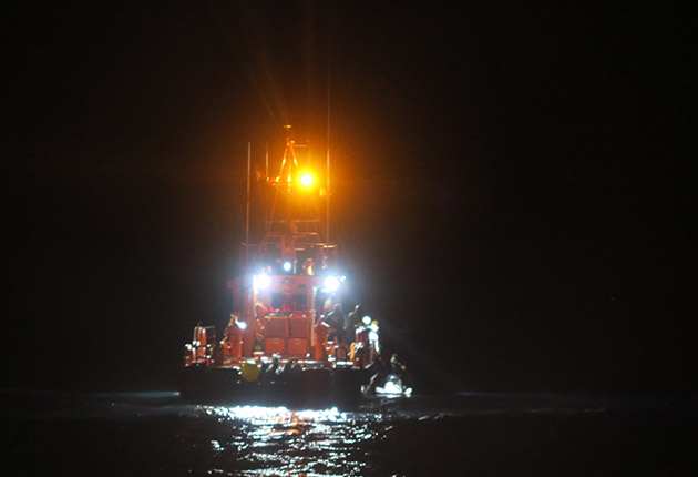 Migrants at sea being rescued by a lifeboat