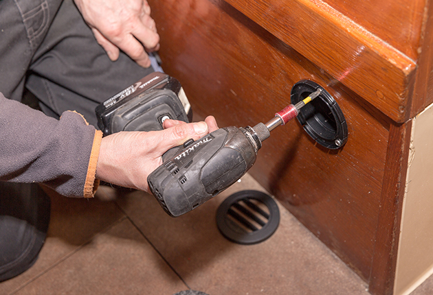 A man drilling a hole to fit a vent for a diesel heater on a boat