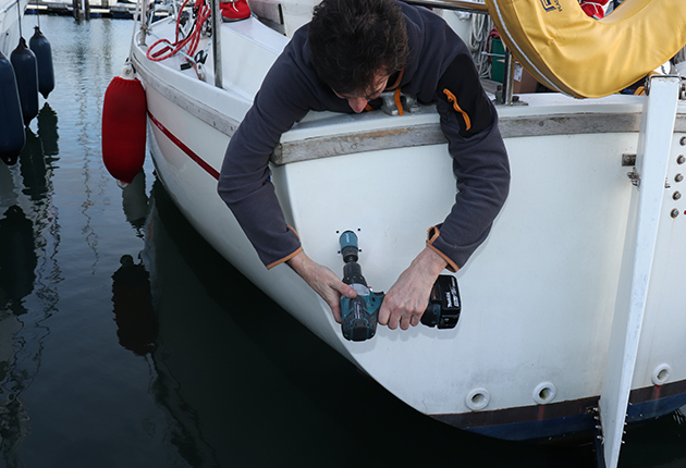 A man drilling a hole in a yacht to fit a heating system