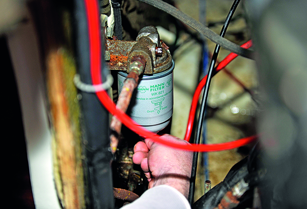 A man Change the primary filter on a boat engine
