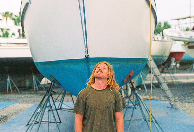 Elliott Smith standing underneath the bow of his boat