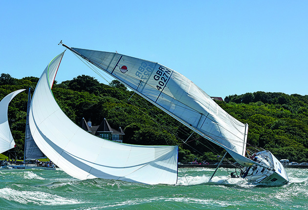 Preventing the spinnaker from blowing to windward is key via clew control when downwind sailing.