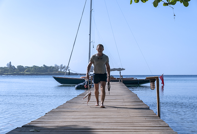 Daniel Craig walking down a jetty with a Spirit 46 moored in the backgrond