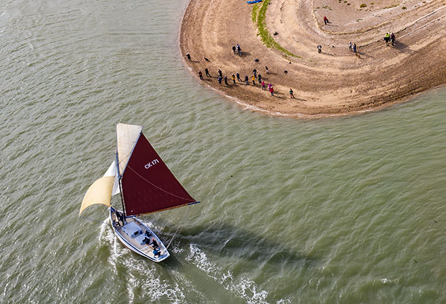 Oyster smack Peace sails past East Mersea Stone on the River Blackwater in Essex, watching by a crowd of spectators