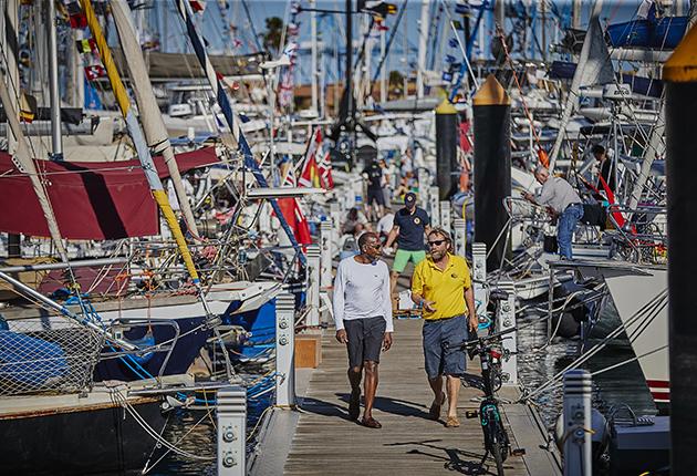 Skippers walking down pontoons in the ARC village