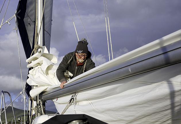 Pat Lawless folding down his mainsail