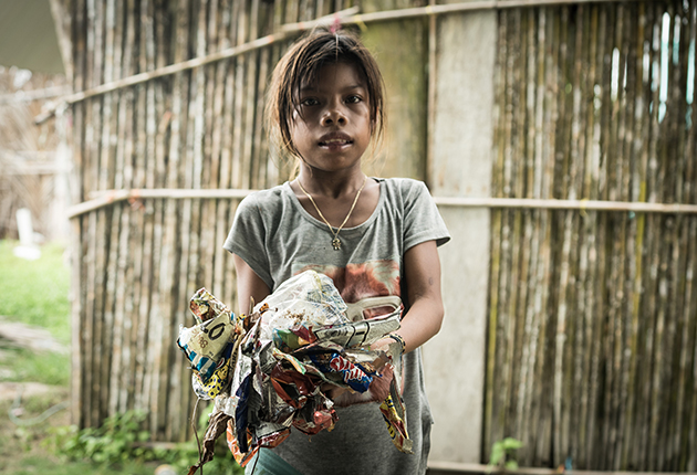 A chid carrying plastic and waste paper in the San Blas isands