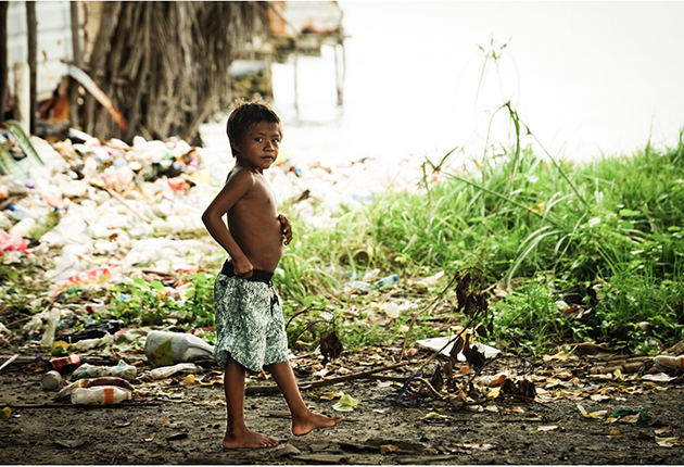 A child standing next to plastic pollution in the San Blas islands