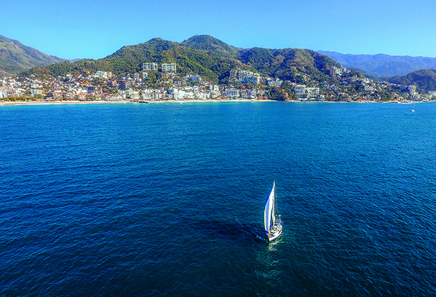 A yacht with white sails sailing in Mexico's Bahia de Banderas