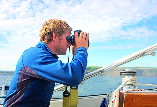 A man using binoculars to do some bird watching from a boat