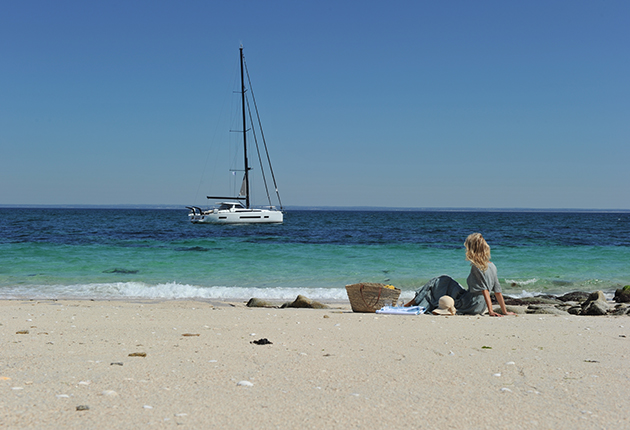 Anchoring problems solved: A woman looking at a boat anchored in the bay