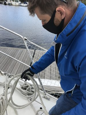 A skipper wearing a mask and gloves to protect against COVID 19 transmission handling deck gear