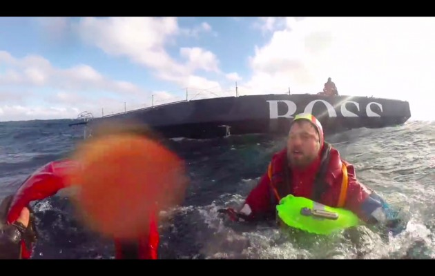 Alex Thomson swims towards a Spanish Coastguard rescue swimmer