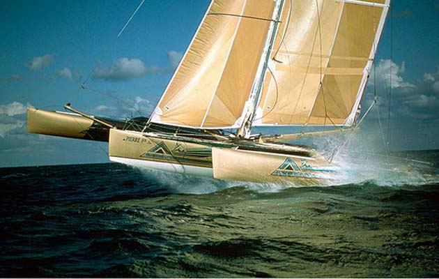 """19. Pierre 1er. 1989, Van Peteghem& Lauriot Prévost: Beautiful and radical, the golden Pierre 1er was the first ORMA 60 and won the 1990 Route du Rhum with Florence Arthaud. Vincent Lauriot Prévost recalls: """"I think in ocean racing the first big change was to fly the hull with a trimaran as if with a catamaran."""" Pierre 1er was swiftly followed by Primagaz, the first big tri to sail on one float. Photo: Jacques Vapillon."""