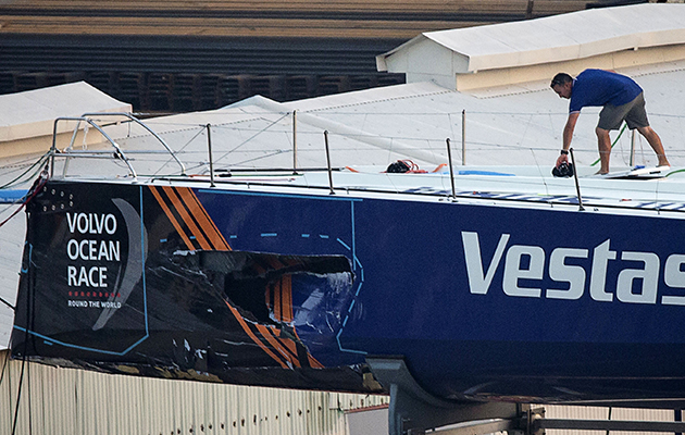A crew member of the Vestas 11th Hour Racing team walks on their damaged yacht, as it sits in a dock for repairs after a collision with a fishing vessel during the fourth leg of the Volvo Ocean Race, Photo: VIVEK PRAKASH/AFP/Getty Images