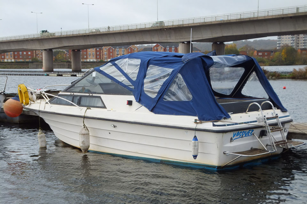 A white motor boat with a blue canopy