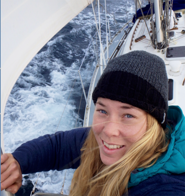 Susie Goodall in a black hat and blue jacket up the mast of her Rustler 36