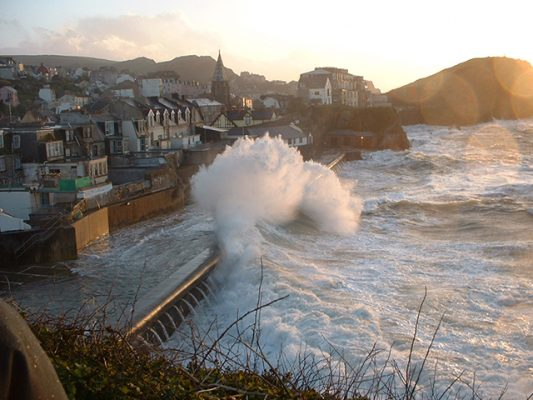 A large wave hits a beach in Devon