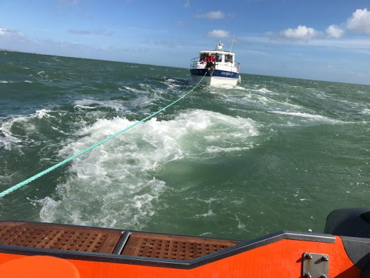 A broken down cabin cruiser boat is towed by a lifeboat