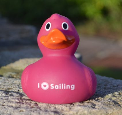 A purple rubber duck with ilovesailing on its chest