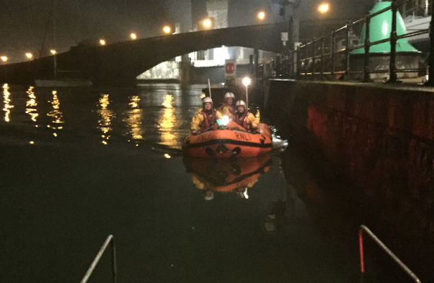 A lifeboat with men inside on the water at Conwy