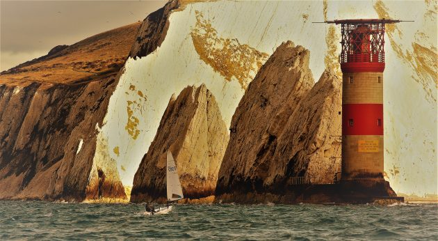 person sailing near cliffs