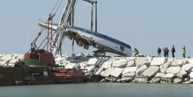 A crane lifts up the remains of a Bavaria Cruiser 50 after it was wrecked at Rimini