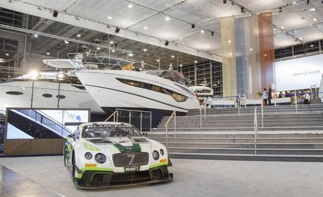 A Bentley car in front of a luxury yacht
