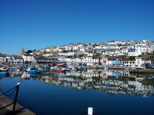 A harbour at Brixham during the summer, with boats moored