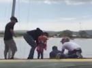 Men rescue children from a stricken yacht